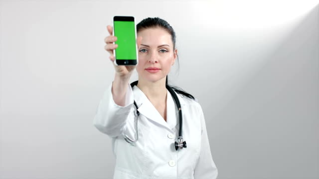 Female doctor showing phone green screen video