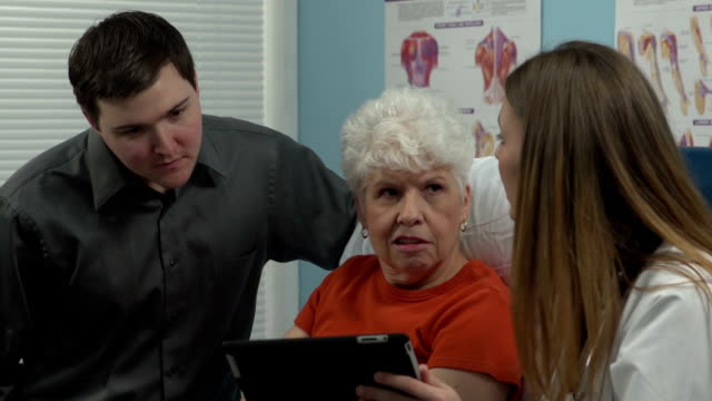 Female doctor showing the patient and her grandson a chart video