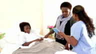 Female doctor with African mother and daughter in hospital video