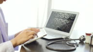 Female Doctors Examining image X-Ray MRI On a Tablet with Laptop and pill bottle video