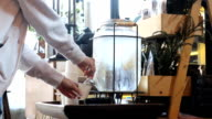 Female drinking cold water from glass tank machine video