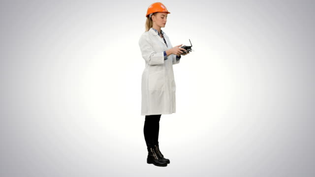 Female engineer correct parts of an object using remote controller on white background video