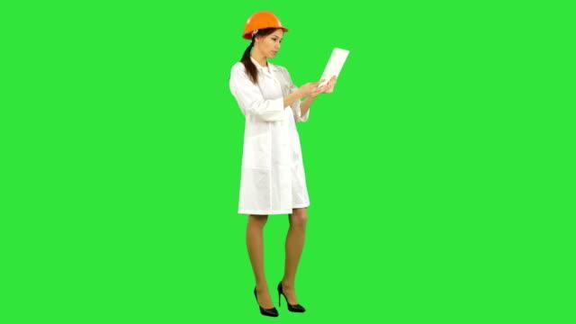 Female engineer in helmet having video call via tablet on a Green Screen, Chroma Key video