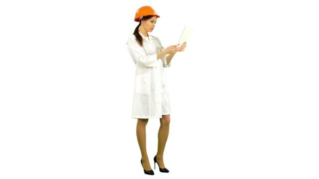 Female engineer in helmet having video call via tablet on white background video
