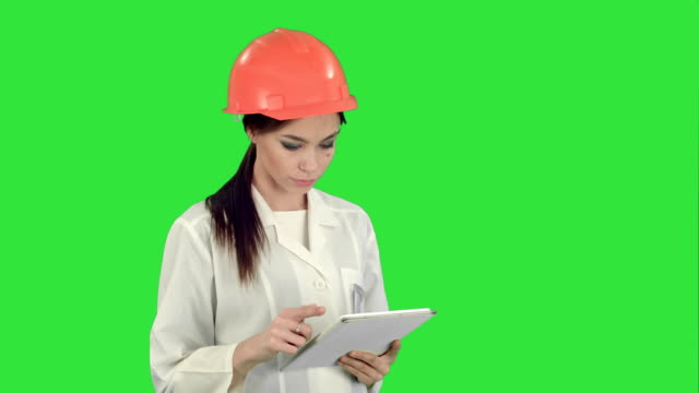 Female engineer in helmet using tablet computer on a Green Screen, Chroma Key video