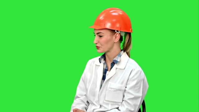 Female engineer in safety helmet sitting and talking on a Green Screen, Chroma Key video