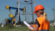 Female Engineer Make Notes Near an Oil Pump, Worker video