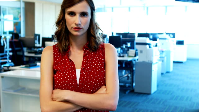 Female executive standing with arms crossed in office video