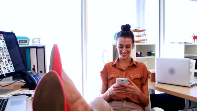 Female executive using mobile phone at her desk 4k video