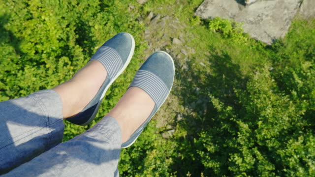 Female feet are flying over the precipice, covered with forest. Going on the ski lift, in the frame you can see only the legs in the shoes video