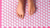 Female feet gently tread on acupuncture massage mat. Top view video