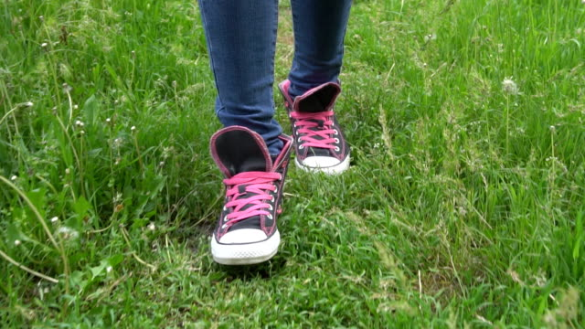 Female feet in sneakers walking on green grass with dandelions. video