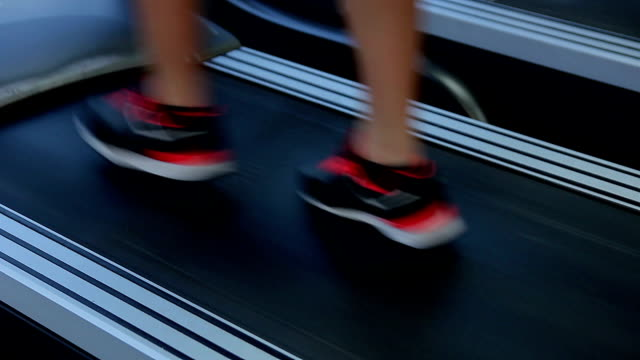 Female feet walking on treadmill. Woman completes workout routine, reaches video