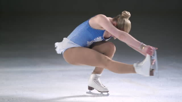 SLO MO LD Female figure skater spinning in sit spin position video