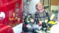 Female firefighter standing beside fire engines video