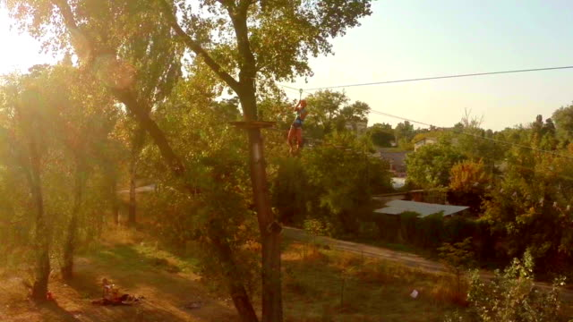 Female flying zipline high above the ground, active rest, sports video
