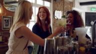 Female Friends Enjoying Drink In Cocktail Bar Shot On R3D video