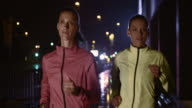SLO MO Female friends jogging in the city at night video