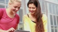 Female friends playing with ipad video