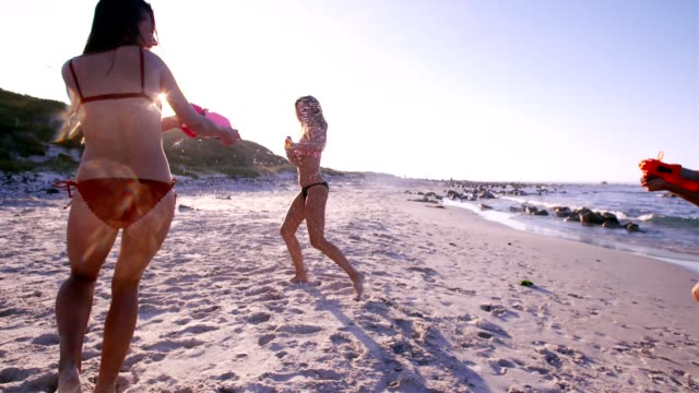 Female friends playing with water guns on the beach video