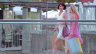 SLO MO Female friends walking across a bridge with shopping bags video