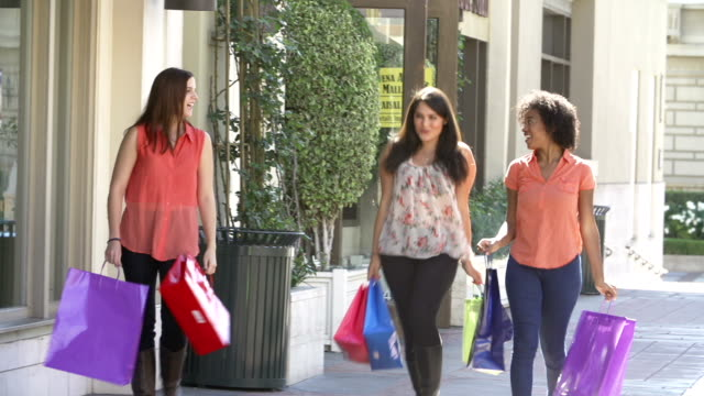Female Friends Walking Through Mall With Shopping Bags video
