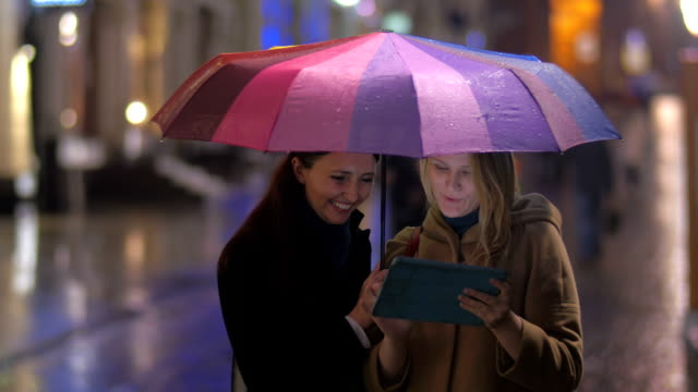 Female Friends with Tablet under an Umbrella video