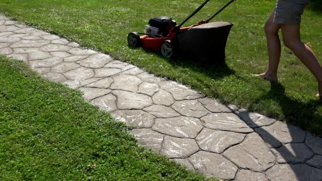 female gardener woman push mower cut grass near stone cobbled path. FullHD video