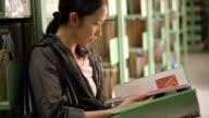 Female, girl student stand beside bookshelves, reading books video