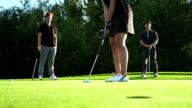 Female golfer makes a putt. video