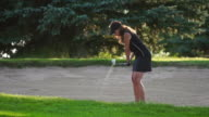 Female golfer shoots from a sand trap video