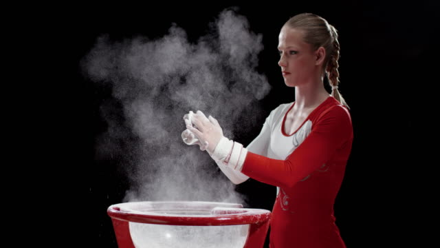 SLO MO Female gymnast clapping her wrapped hands over the chalk bowl video