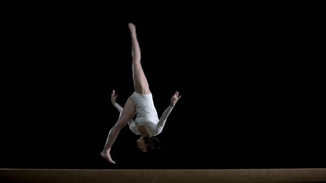 SLO MO Female gymnast doing a flip on balance beam video