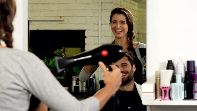 Female hairdresser blow drying her client hair video