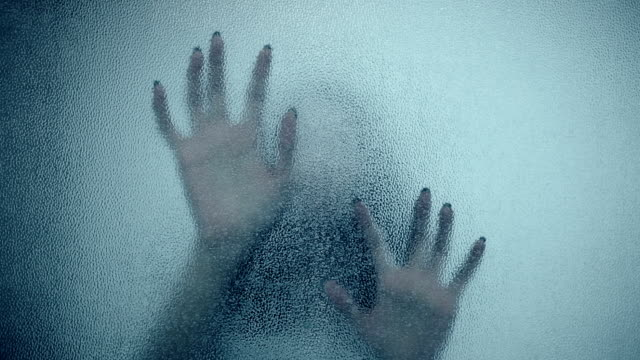 female hand and head, spooky shadows on the glass wall, in full HD, Horror movie scene video