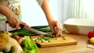 Female hand cutting green onions on board with knife video