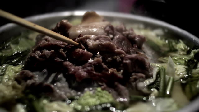 Female hand flipping the meat on a hot pan with smoke video