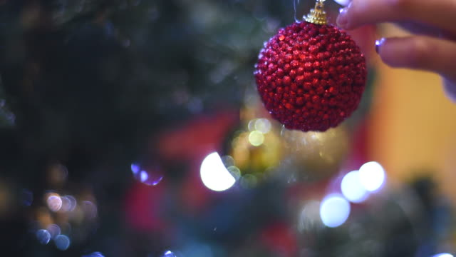female hand hangs a Christmas ball on the Christmas tree video