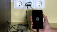 female hand holding smart phone plugged with wall charger video