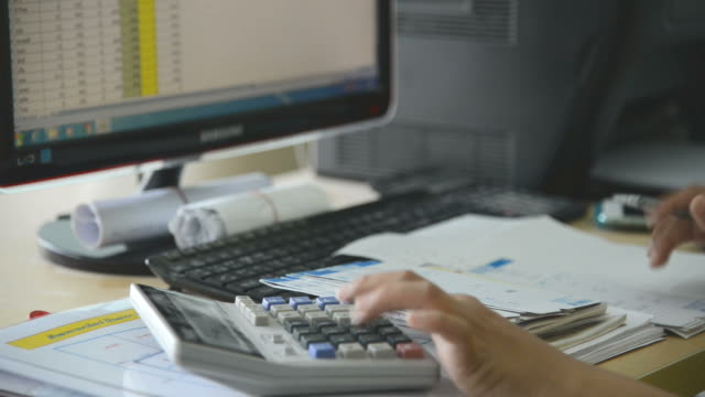 Female hand in Working Payroll workers. Calculation at office video