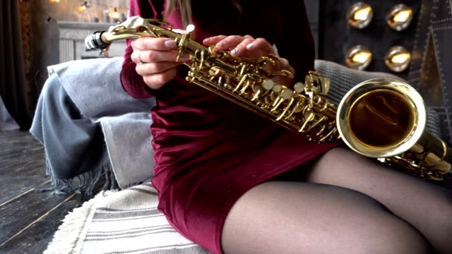 Female hand is stroking a saxophone. Saxophone lies on a woman's lap video