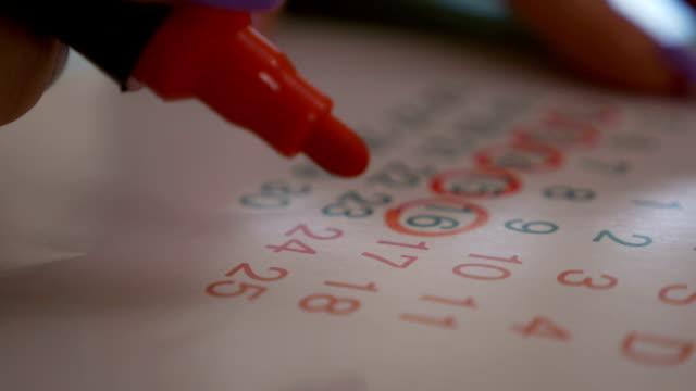 Female hand marking dates on calendar planning birth control video