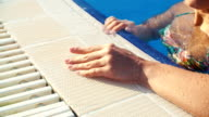 female hand on edge of pool on Sunny summer day closeup video