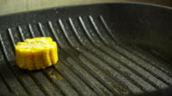Female hand placing corn cob pieces on hot grill pan video