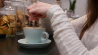 Female hand pour sugar into a cup of coffee video