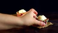 Female hand take away cupcake on wooden background. Sweet dessert video
