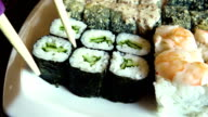 Female hand takes sushi rolls video