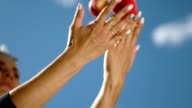 Female hand throw up apples on a background of blue sky. Slowmotion video