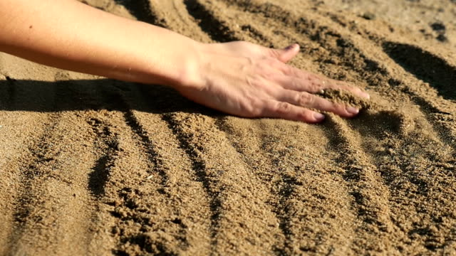 Female hand touching sand video