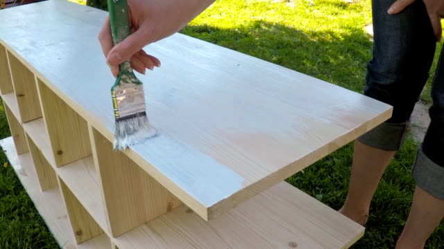Female hand with brush painting wooden furniture. video